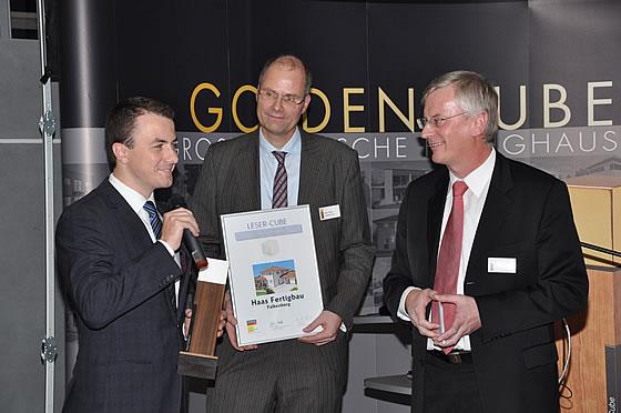 Marc Stilke (mi.), CEO der Immobilien Scout GmbH, und Harald Fritsche (re.), Geschäftsführer des Fachschriften-Verlags,  überreichen den Leser-Cube an Xaver A. Haas, Geschäftsführer der Haas Fertigbau GmbH - Foto: Haas