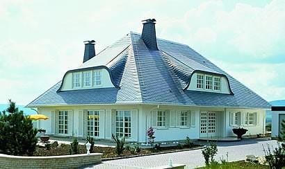 OKAL hat den zeitlosen Klassiker Residenz wieder: Die OKAL Residenz mit typischem Schiefer-Walmdach und Sprossenfenstern mit Fensterläden wurde komplett neu konzipiert und ist das richtige Haus für alle Menschen, die zeitlose Eleganz bauen möchten.Foto: OKAL Haus