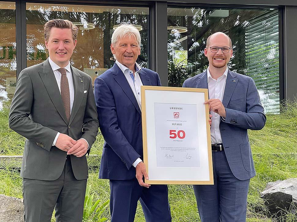 Christian Huf (l.) und Benedikt Huf (r.) erhielten die Jubiläumsurkunde von BDF-Präsident Hans Volker Noller (m.). Foto: HUF HAUS
